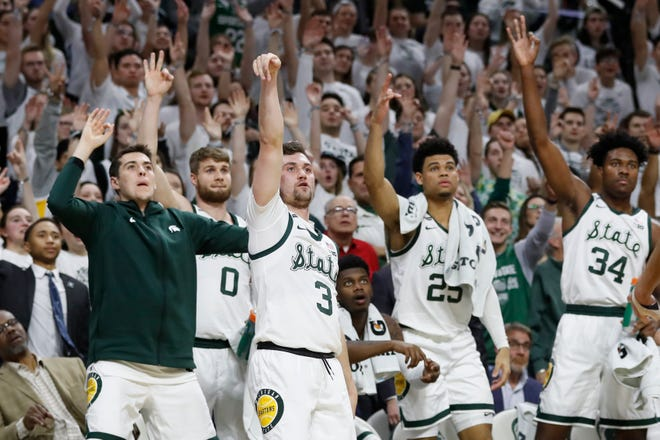 Fans and the Michigan State bench watch as guard Foster Loyer (3) hits a 3-point basket during the second half of an NCAA college basketball game against Northwestern, Wednesday, Jan. 29, 2020, in East Lansing, Mich. (AP Photo/Carlos Osorio)