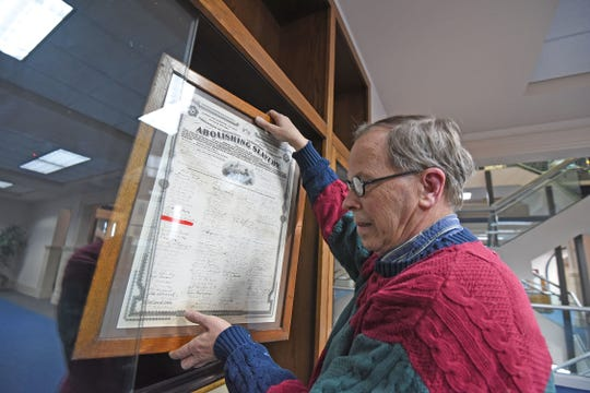 Scott Schaut handles a piece of the Black History Month exhibit at the Mansfield/Richland County Library. The material came from the Mansfield Memorial Museum.