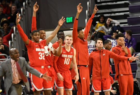 The Ohio State Buckeyes bench celebrates a 3-point basket against the Northwestern Wildcats during the second half at Welsh-Ryan Arena on Sunday.
