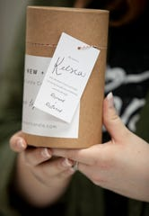 Kelsea Vaughn of Memphis shows a card on the side of the candle packaging at RE+NEW+ALL candle company on Jan. 28.