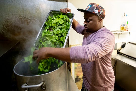 Chef de cuisine Kevin Sullivan puts mustard greens in a pot Thursday, Jan. 30, 2020, at Tsunami in Memphis. Sullivan started at the restaurant in 2002 as a dish washer.