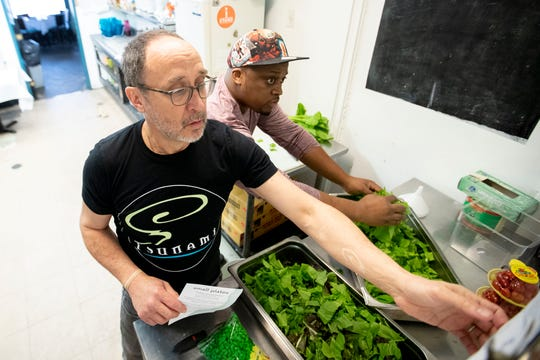 Kevin Sullivan (right) prepares greens as Ben Smith looks over the weekend menu Thursday, Jan. 30, 2020, at Tsunami in Memphis.