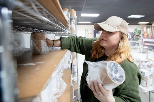 Kelsea Vaughn of Memphis pulls candles from a shelf for inspection and packaging on Jan. 28.