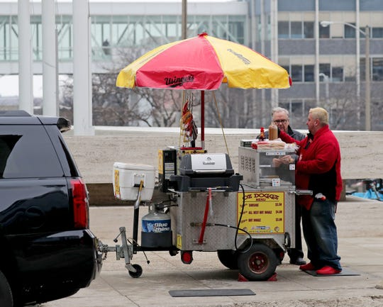 """""""If it's above 30 degrees I'm out here,"""" says Oz Becklund, right, owner and operator of Oz Doggz hot dog stand outside the U.S. Bank building on the corner of East Wisconsin Avenue and North Van Buren Street in Milwaukee on Thursday, Jan. 30, 2020. According to the National Weather Service, temperatures are expected to stay above freezing for the next several days with a high of 45 degrees on Sunday."""