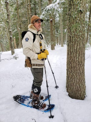 Jon Michels pauses while snowshoeing through the Apostle Islands National Lakeshore on the Bayfield peninsula. Michels leads snowshoe tours in the area through his company Wolftrack Guides.