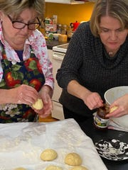Barbara Mlot (left) and Edyta Mlot fill paczki in preparation for frying. The Mlot family makes the Polish treat an annual tradtion.