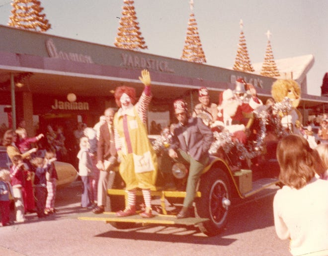 Ronald McDonald waves at a crowd during a parade through Normandale.