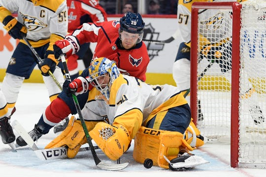 Washington Capitals center Lars Eller (20) and Nashville Predators goaltender Juuse Saros (74) battle for the puck during the second period on Wednesday.