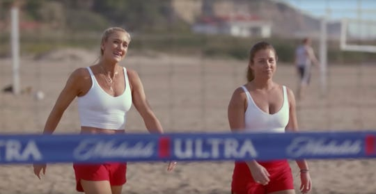 This undated image provided by Michelob ULTRA shows Kerri Walsh Jennings, left, and former FGCU volleyball star Brooke Sweat in a scene from the company's 2020 Super Bowl NFL football spot. Michelob Ultra stresses its low calories and low carbs in an ad that shows talk show host Jimmy Fallon and wrestler John Cena working out.