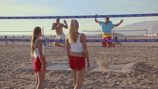 This undated image provided by Michelob ULTRA shows from left, Brooke Sweat, John Cena, Kerri Walsh Jennings and Jimmy Fallon in a scene from the company's 2020 Super Bowl NFL football spot.  Michelob Ultra stresses its low calories and low carbs in an ad that shows talk show host Jimmy Fallon and wrestler John Cena working out.