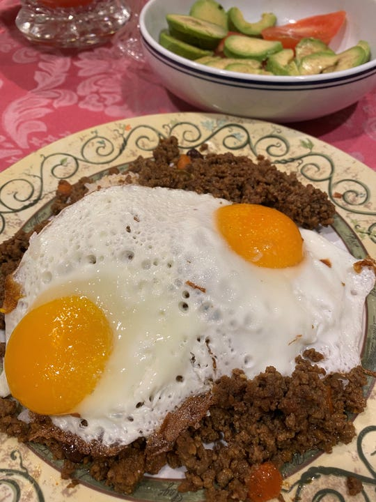 Picadillo with Spanish olives and raisins over a bed of rice topped with two sunny-side eggs that the wife of Mayor Carlos Rendo of Woocliff Lake served for dinner one night