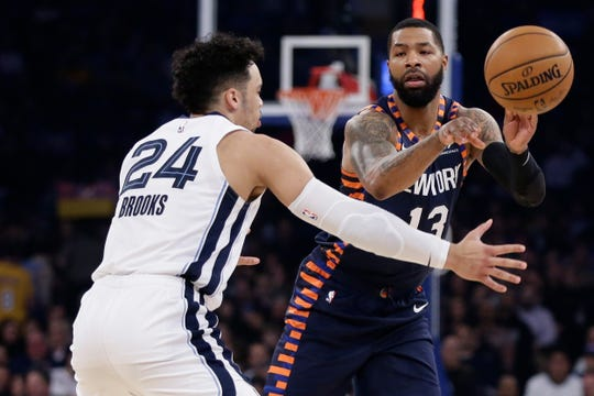 New York Knicks' Marcus Morris Sr. (13) passes the ball away from Memphis Grizzlies' Dillon Brooks (24) during the first half of an NBA basketball game Wednesday, Jan. 29, 2020, in New York.