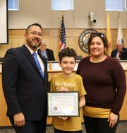 Andrew Mansur, center, is the first Overcomer Award recipient, pictured with Commissioner Sanchez to his left and his mother, Tanya Mansur, right.