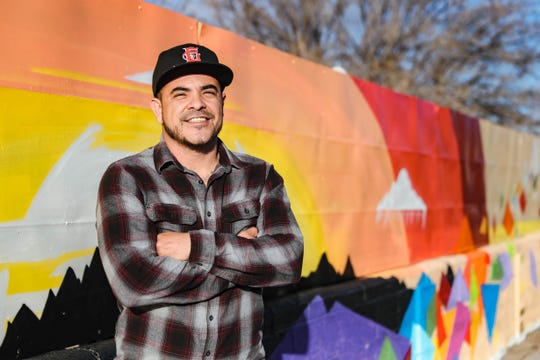 Robert Azure stands Friday, Jan. 30, 2020, next to a mural he, along with artistic partner Cameron Vigil, painted in Las Cruces. The mural is at the corner of Idaho Avenue and Luna Street.