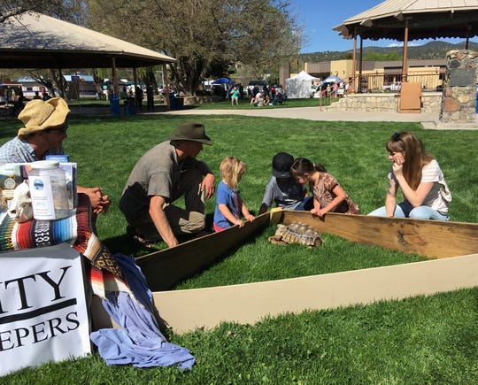 Indi Blake of the Silver City Watershed Keepers introduces children to Flower the Tortoise at Gila Earth Day 2019.