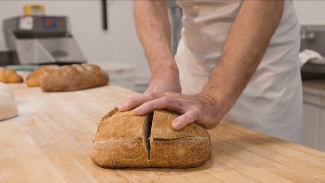 Trent Wester, co-owner of Thunderbird Bakery, 1335 Planeview Drive, Oshkosh, cuts into sourdough bread he made.