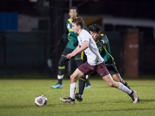 Logan Tyree (4) moves past Mario Cardenas (14) during the Tate vs Catholic boys soccer game at Pensacola Catholic High School in Pensacola on Wednesday, Jan. 29, 2020.