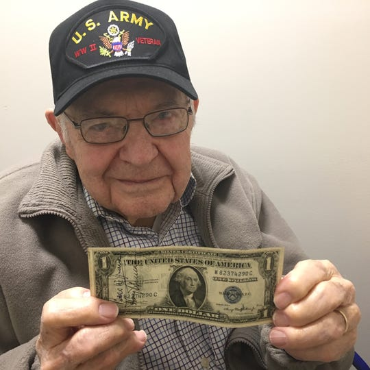 David Houck holds up a dollar bill that was signed for him by President Harry S. Truman. While he was recovering in Washington D.C. in 1945, Houck and other service members were invited to a tea at the White House to meet the president and first lady.