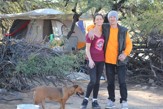 Robin Miller and Bryan Cowens, homeless for 10 years, found shelters in a tent in a dusty retention basin in Goodyear.