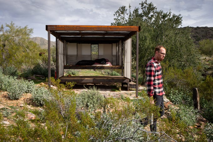 Michael Simmons, a fourth year, walks past The Loft shelter on Jan. 29, 2020, at the School of Architecture at Taliesin West in Scottsdale.