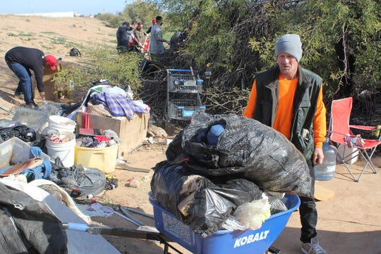 Bryan Cowens helps clean up an area in Goodyear where homeless people camp, along with staff and volunteers at Phoenix Rescue Mission.