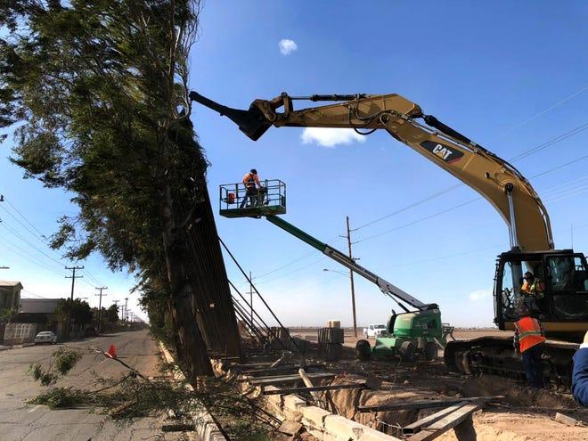Fotografía cedida por Rafael Torres donde se muestra a una grúa mientras intenta sostener trozos del muro fronterizo que cayeron este miércoles en la frontera de Calexico, California.