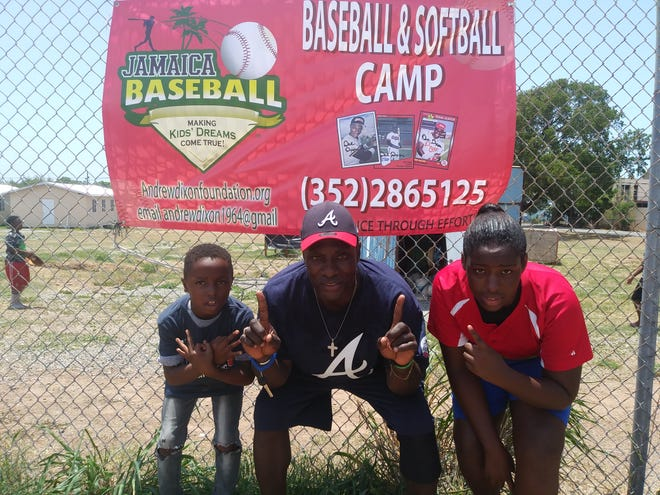 Poughkeepsie product and former professional baseball player Andrew Dixon poses between two participants at his youth baseball and softball camp in Jamaica.