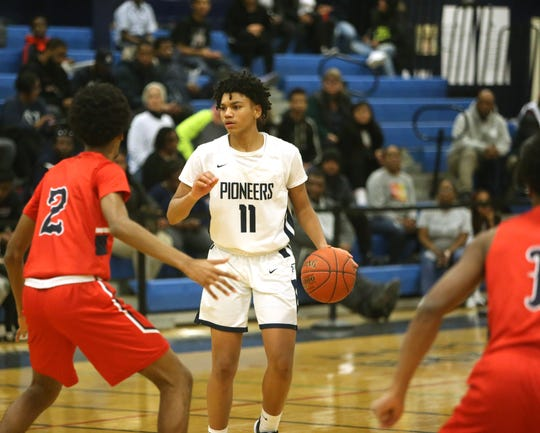 Poughkeepsie's Javel Cherry dribbles up court against the Peekskill defense during Wednesday's boys basketball game.