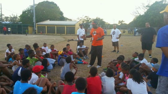 Andrew Dixon, center, speaks to a group of small children in his native Jamaica during one of his baseball clinics.