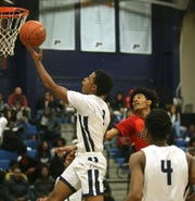 Poughkeepsie's JaDeion Buckley takes a jump shot ahead of Peekskill's LaQuan Jenkins during Wednesday's game on January 29, 2020.