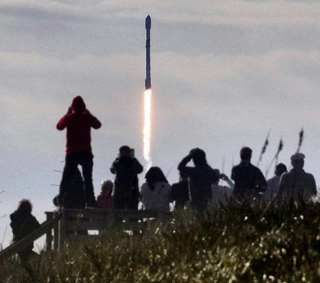 In this view from Playalinda Beach at Canaveral National Seashore, visitors watch a SpaceX Falcon 9 rocket launch from Cape Canaveral Air Force Station carrying 60 Starlink satellites, Wednesday, Jan. 29, 2020. It's the fourth launch of satellites in the SpaceX Starlink mission. (Joe Burbank/Orlando Sentinel/TNS)