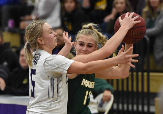 Bishop Manogue's Kenna Holt is pressured by Spanish Spring's Megan Gower as she looks to pass the ball on Jan. 9.
