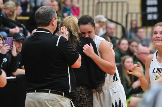 Winchester head coach Holly Gutierrez embraces senior Maddie Lawrence as she checks out at Winchester Fieldhouse for the final time.
