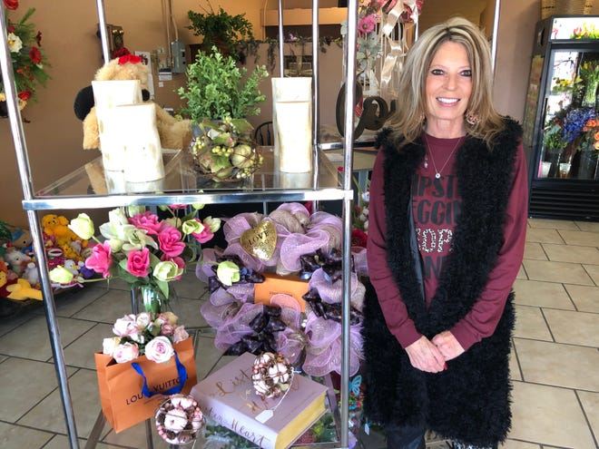 Owner of Pam's Petals, Pamela Bump, poses next to her Louis Vuitton creations.