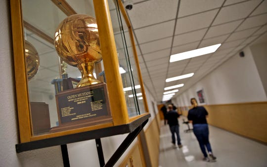 A trophy from the 2009-2010 junior high basketball season sits in a case just outside the gym at the Olfen school on Friday, Jan. 24, 2020.