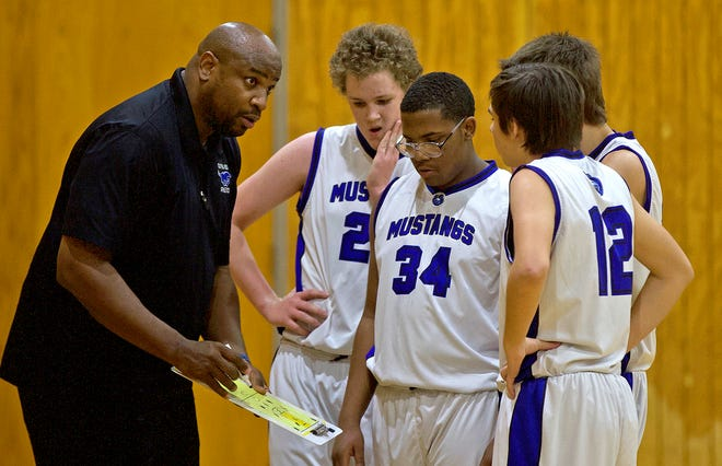 Olfen boys basketball coach Travis Tennison, far left, coaches the team during a timeout as they play Mullin on Friday, Jan. 24, 2020.