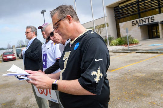 "Members of SNAP, the Survivors Network of those Abused by Priests, including John Gianoli, left, John Anderson, Richard Windmann, and Kevin Bourgeois, read a press release from the New Orleans Saints as they hold signs during a conference in front of the New Orleans Saints training facility in Metairie, La., Wednesday Jan. 29, 2020.  The pro football team acknowledged last week that its front office helped church leaders deal with the public relations fallout that followed the publishing a list of local clergymen the archdiocese deemed ""credibly accused"" of sexually abusing children.  (AP Photo/Matthew Hinton)"