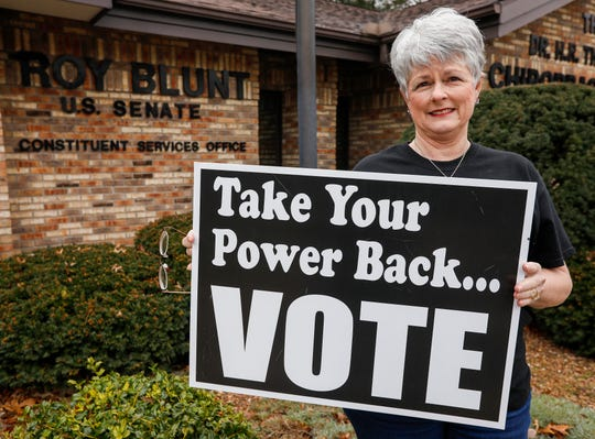 """Activist Laura Umphenour holds up a """"Take your power back... VOTE"""" sign in front of U.S. Senator Roy Blunt's office in Springfield on Thursday, Jan. 30, 2020."""