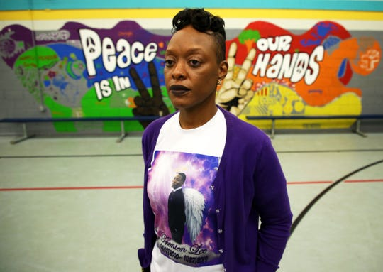 Coressa Reed, who is the mother of Trent Lee, a 19-year-old who was shot and killed in November, poses for a photo in front of a mural on the wall of the gym at the Palmer Munroe Teen Center.