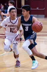 Redwood's Nahir Karimj drives against Mt. Whitney's Rudy Huerta in a West Yosemite League high school boys basketball game on Wednesday, January 29, 2020.