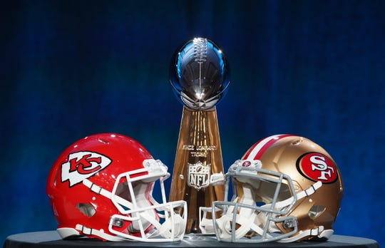Jan 29, 2020; Miami, Florida, USA; Helmets for the Kansas City Chiefs and San Francisco 49ers are placed in front of the Vince Lombardi Trophy during a press conference before Super Bowl LIV at Hilton Downtown. Mandatory Credit: Kirby Lee-USA TODAY Sports