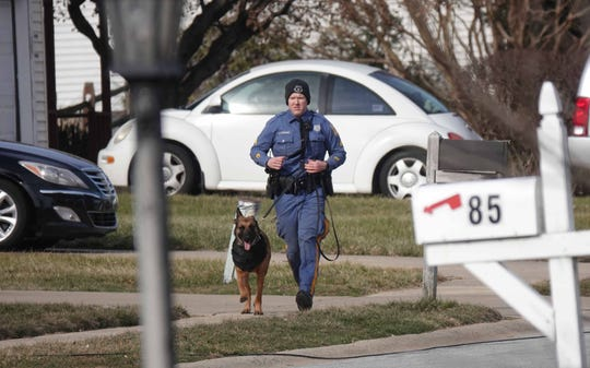 A Delaware State Police K-9 officer and his dog run down the unit block of Bunker Hill in the Penn Acres South development Thursday morning while responding to a standoff.