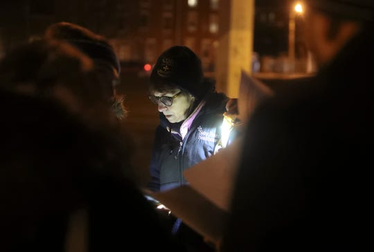Dr. Sandra Gibney asks survey questions of people spending the night under I-95 in Wilmington as she joins a group of volunteers and housing advocates in conducting an annual census of people without housing in Delaware Wednesday evening.