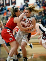 Sheridan's Bailey Beckstedt, left, tries to pull the ball away from New Lexington's Kim Kellogg on Wednesday night in New Lexington.