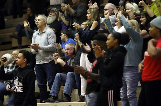 Mark Dempsey (seated) gives his son Marcus a quick fist pump after Marcus broke Muskingum University's men's basketball scoring record Wednesday night. Marcus passed his father on the Muskie's all-time scoring list earlier this year. The senior Dempsey currently sits at 7th all-time for the school.
