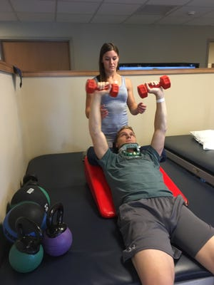 Alise Willoughby (back) helps her husband Sam Willoughby (front) with a rehab workout on his journey to recovery following a 2016 accident.