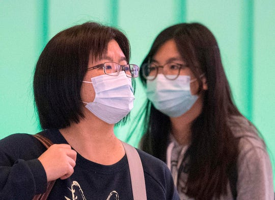 Passengers wear face masks to protect against the spread of the Coronavirus as they arrive on a flight from Asia at Los Angeles International Airport, Calif. on Jan. 29, 2020.