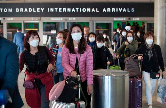 Passengers wear masks to protect against the spread of the coronavirus as they arrive on a flight from Asia at Los Angeles International Airport on Jan. 29, 2020.