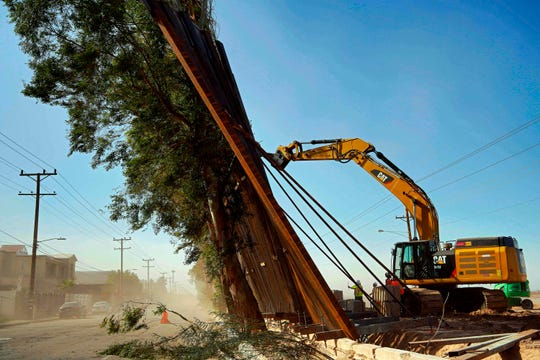 A construction crew works on a fallen section of the US-Mexico border wall as seen from Mexicali, Baja California state, Mexico, on January 29, 2020.