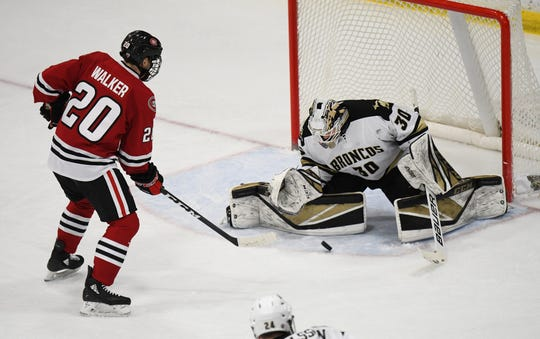Western Michigan men's hockey goalie Brandon Bussi (No. 30) stops a shot by St. Cloud State forward Nolan Walker (No. 20) during a game in Kalamazoo, Michigan, on Saturday, Jan. 25, 2020.